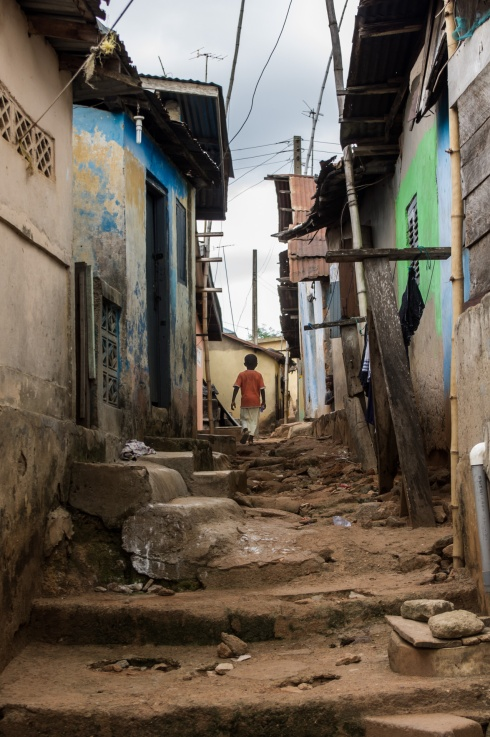 A child walks through a narrow lane in one of the poorer parts of Agona Swedru, Ghana.