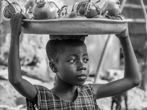 A child sells vegetables in Bobikuma, Ghana.