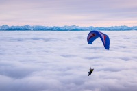 A praglider practices over a sea of clouds on Mount Chasseral, Switzerland.
