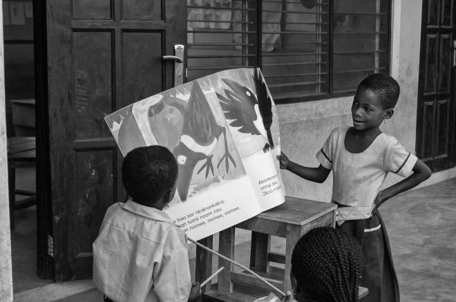 Children in a Ghanaian preschool read a story book with their teacher.